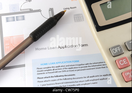 Home loan application form with calculator and pen nearby - Stock Photo
