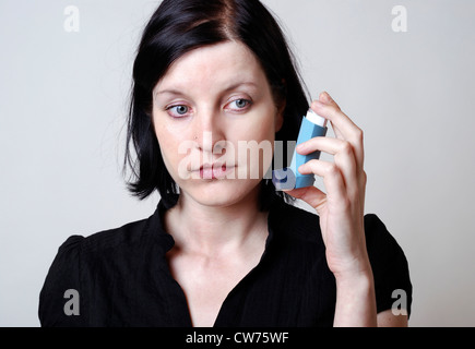 Woman is holding asthmaspray in her hand - Stock Photo