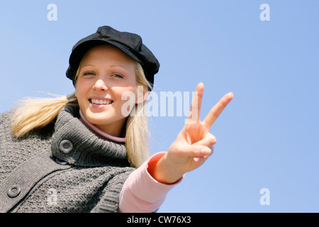 young blond girl with cap, showing the victory sign - Stock Photo