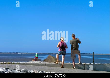 tourists standing on mole, Germany, Lower Saxony, Neuharlingersiel - Stock Photo