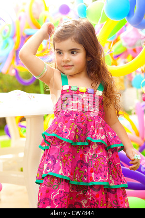 Beautiful little girl on birthday party, colorful balloons holiday decoration, pretty small female child play game - Stock Photo