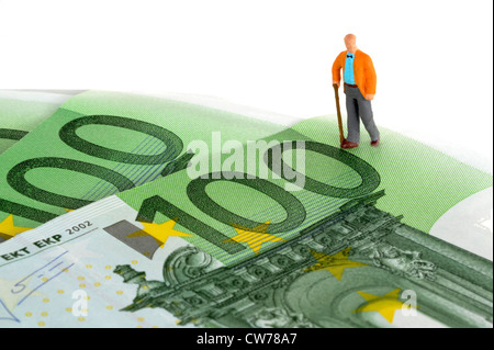 symbolic picture for pesion and provision for one's old age, little figure on bank notes - Stock Photo