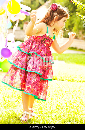 Nice small girl dancing outdoors, little female child enjoying her 3-year old birthday party, colorful balloons - Stock Photo