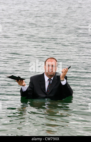 businessman withmobile phone and diarykeep his head above water - Stock Photo