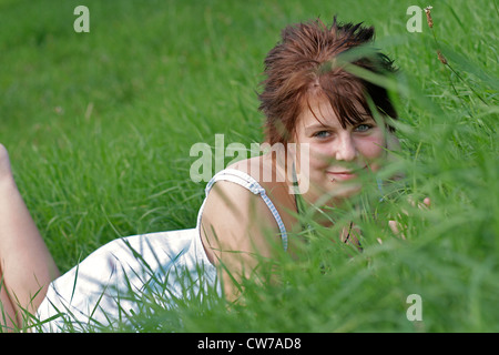 young woman in summer skirt lying in meadow, Germany - Stock Photo