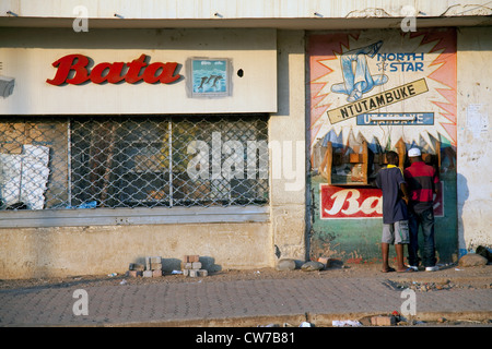 street scene in the capital with little shops near the main market and two men using a public phone, Burundi, Bujumbura - Stock Photo