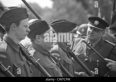 Re-enactor playing 1940's British and American Army Soldiers with others on parade - Stock Photo