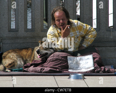 Homeless person with dog is asking for money on a bridge over the Alster in the city of Hamburg, Germany, Hamburg - Stock Photo