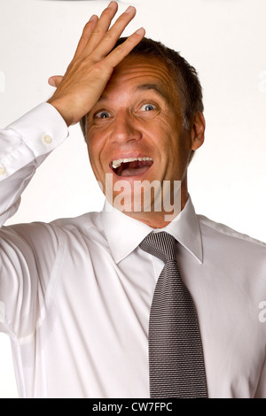 Old businessman with a white shirt and tie is hitting his hand on the forehead - Stock Photo