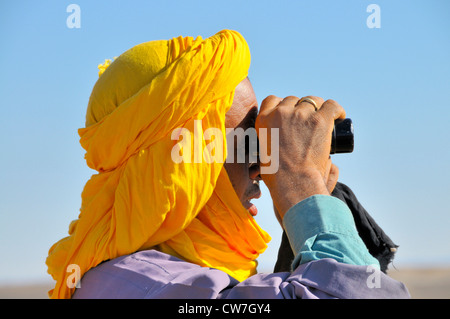 berber with traditional tagelmust searching for lost animals with a field glasses, Morocco, Erg Chebbi, Sahara - Stock Photo