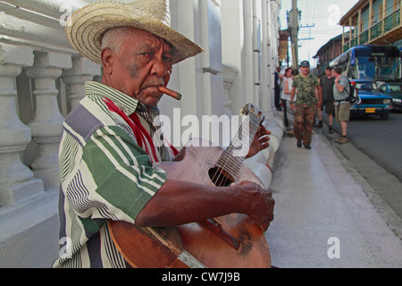 old man standing at a roadside with a straw hat, a cigar in the mouth and a guitar, Cuba, Santiago de Cuba - Stock Photo