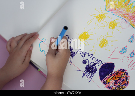 A close up of a child's hands drawing a picture. - Stock Photo