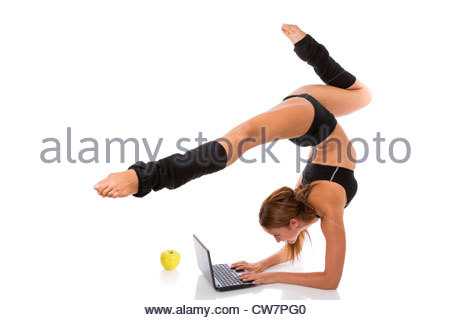 Athletic woman standing in flexible posture and typing on laptop keyboard, isolated on white. - Stock Photo