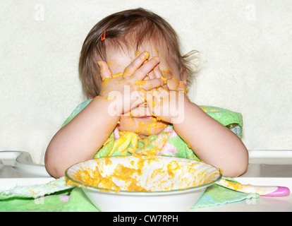 Funny baby with food covered face by putting her hands over her eyes to play picaboo during mealtime, wrong time - Stock Photo