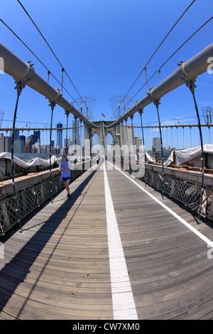 Jogger and tourists on Brooklyn Bridge New York City - Stock Photo