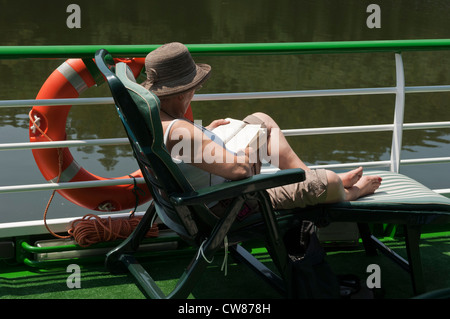 Cruise ship passenger on deck, reading a book. Douro Valley. Portugal - Stock Photo