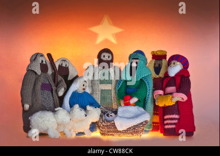 Knitted nativity scene depicting the birth of Jesus on an orange background with a yellow star above the figures - Stock Photo