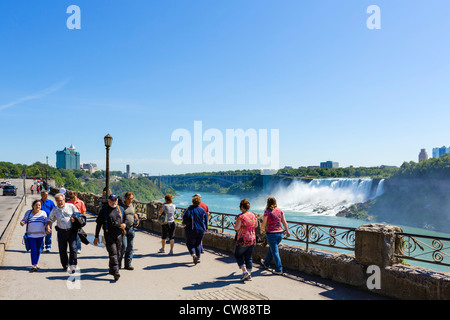 Tourists on path with the American Falls behind, Niagara Falls , Ontario, Canada - Stock Photo