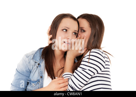 teenager whispering news to her sister on white background - Stock Photo