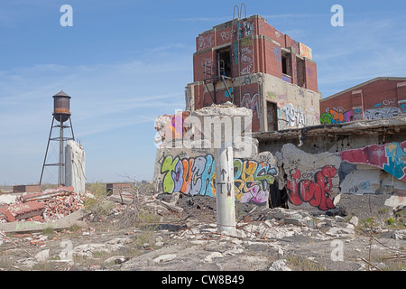 Roof top of an abandoned car manufacturing plant in Detroit Michigan. The ceiling supports have toppled over graffiti - Stock Photo