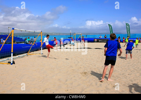 Young boys take part in the Dorset Sports Challenge by playing beach soccer at Weymouth - Stock Photo