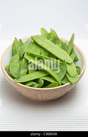 Mange Tout, Sugar snap Peas in bowl on plain Background - Stock Photo