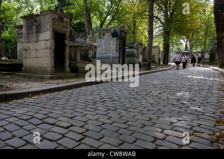 Wide cobbled avenue in the Pere Lachaise cemetery, Paris. Père Lachaise Cemetery (Cimetière du Père-Lachaise) is - Stock Photo