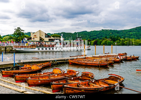 Empty rowing boats drawn up on the shingle beach as trippers board the historic steamer (now diesel), MV Tern, Lake - Stock Photo
