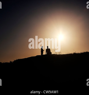 two people standing in the back light on a hill