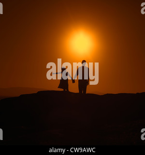 Father and daughter standing hand in hand at sunset on a hill