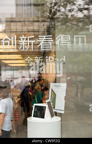 Sign in Chinese advertising the Apple iPhone and iPad at the Apple store in Beijing, China - Stock Photo
