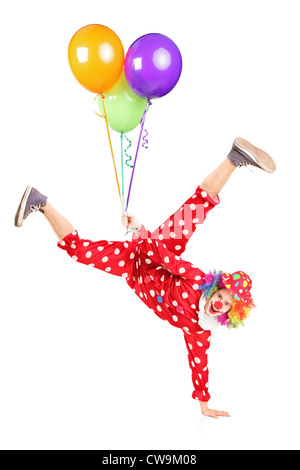 Clown holding balloons and standing on one hand isolated on white background - Stock Photo