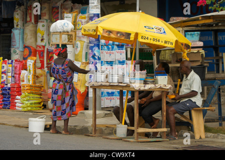 Woman buying from street vendor, Cape Coast, Ghana - Stock Photo