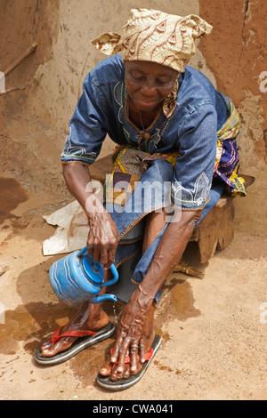 Woman washing her feet outside mud hut, Gambaga, Ghana - Stock Photo