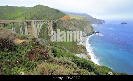 View of concrete arch bridge over gorge with mountains on one side and cliffs down to ocean on the other - Stock Photo