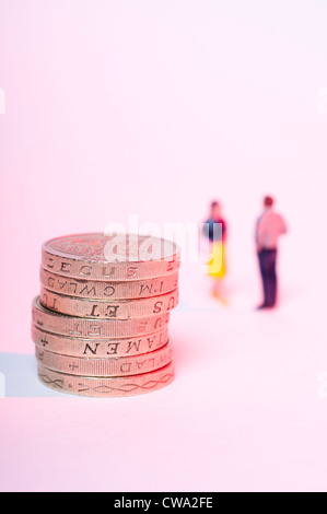 Stacked up one pound coins and blurred couple in background - Stock Photo