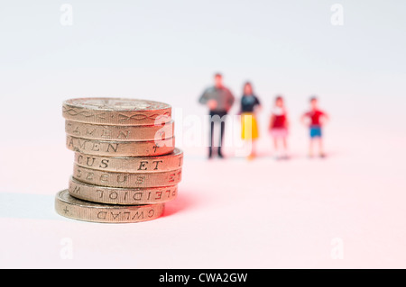 Stacked up one pound coins and blurred family in background - Stock Photo