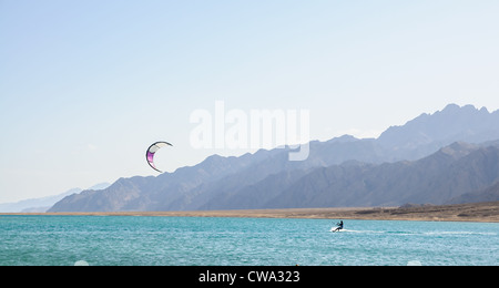 kite-surfer in lagoon surrounded by desert mountains - Stock Photo