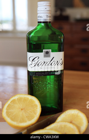 Bottle of Gordon's gin on a table along with a lemon and some slices - Stock Photo