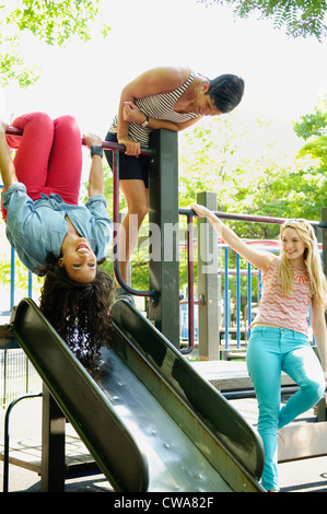 Three adult friends playing on a slide - Stock Photo