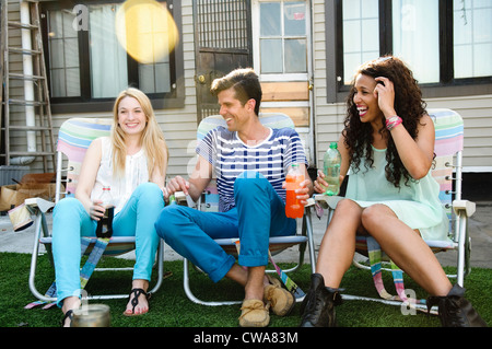 Three friends in deckchairs on roof - Stock Photo