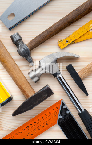 Assorted construction and measurement tools arranged on a wooden surface. Construction, repair or home improvement - Stock Photo