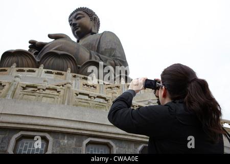 Woman taking photograph of tian tan buddha, hong kong, china - Stock Photo