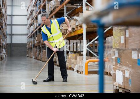 Man sweeping warehouse floor with broom - Stock Photo