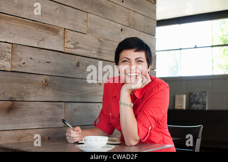 Woman wearing red shirt sitting in cafe, portrait