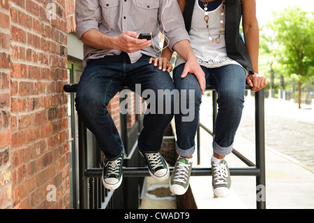 Couple outside building, listening to music on mp3 player - Stock Photo