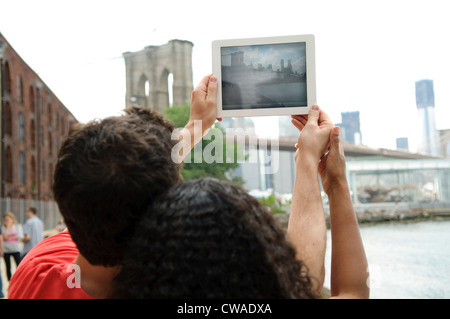 Couple taking picture of Brooklyn Bridge with digital tablet - Stock Photo