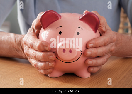 Senior woman holding piggy bank - Stock Photo