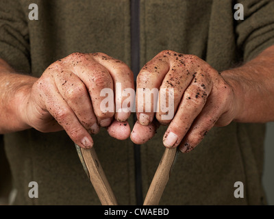 Man leaning with hands on wooden handle - Stock Photo