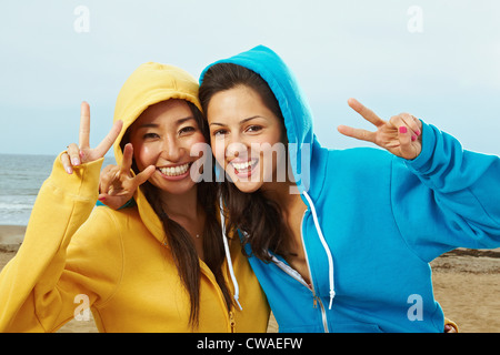 Two young women in hooded tops on beach - Stock Photo